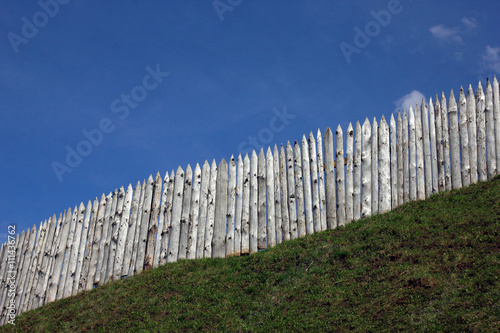 Fotografie, Obraz  the wooden palisade on the green grass shaft of the ancient fort