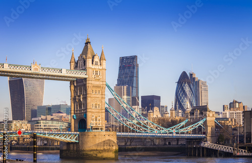 London, England - Iconic Tower Bridge in the morning sunlight with Bank District at background
