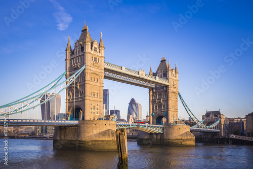 London, England - Iconic Tower Bridge in the morning sunlight with Red Double Decker bus and Bank District at background