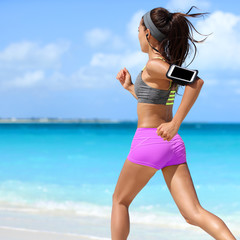 Naklejka Fit woman running working out cardio exercise on summer tropical beach. Unrecognizable athlete runner jogging intense wearing phone armband holder for music motivation listening on smartphone app.