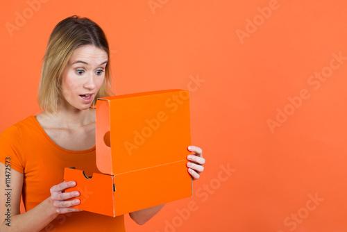 Valokuva  frau schaut erstaunt in schuhkarton