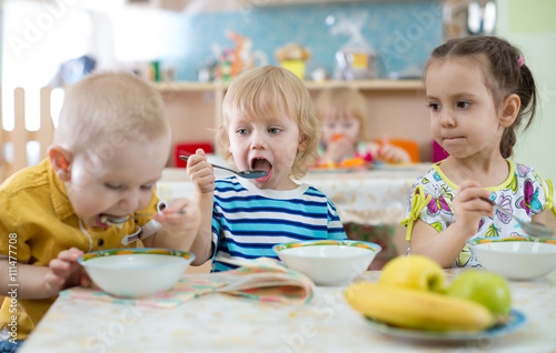 Keuken foto achterwand Kruidenierswinkel group of children eating from plates in day care centre