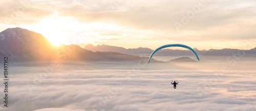 Man paragliding above clouds, Alps, Salzburg, Austria