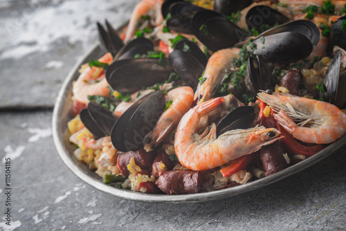 Fotografering Paella in the metal plate on the metal background horizontal