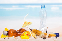 Plastic Bottles, Food Waste, Rubber Duck In  Sand Against  Sea.