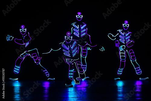 Türaufkleber Karneval dancers in led suits on dark background, colored show