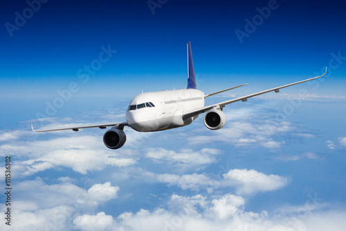 obraz lub plakat Commercial jet plane flying above clouds