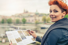 Female Tourist Looking At City Guide