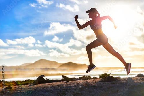 Athlete runner trail running on summer beach. Fit body silhouette of sports Woman in sportswear cap sprinting with energy and motion in outdoors nature training cardio with jogging workout exercise.