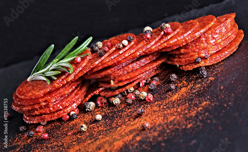 Carta da parati  sausage or salami with fresh herbs colorful seasoning on black stone