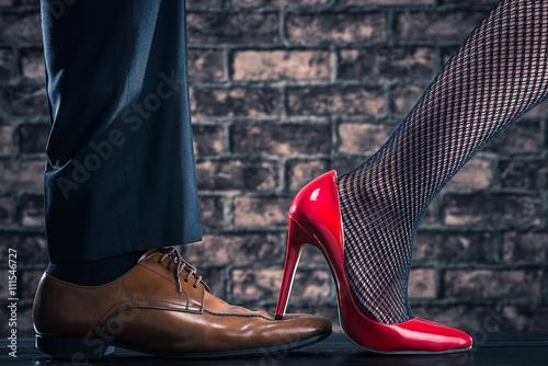 Fotografie, Tablou  赤いハイヒールの女性が男性の革靴を踏んでいる