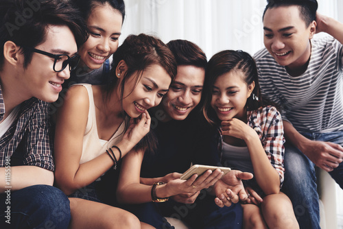Fotografia  Laughing friends watching old funny pictures on smartphone