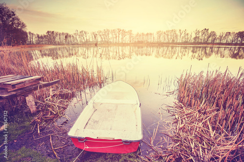 Vintage toned boat by a lake at sunrise