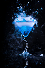 Fototapetablue cocktail with splash and ice vapor