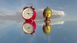 Brass Buddha head sculpture and red clock on mirror under cloudy sunny sky, time lapse 4K