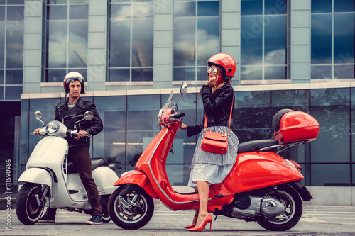 Male and female having fun on moto scooters. Wallpaper Mural