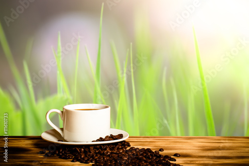Wall Murals Cafe Coffee beans and coffee in white cup on wooden table opposite a