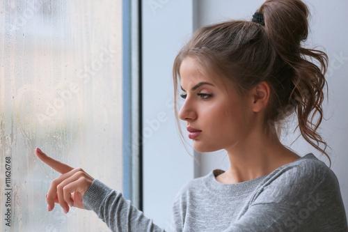 Photo Beautiful young woman sitting on windowsill