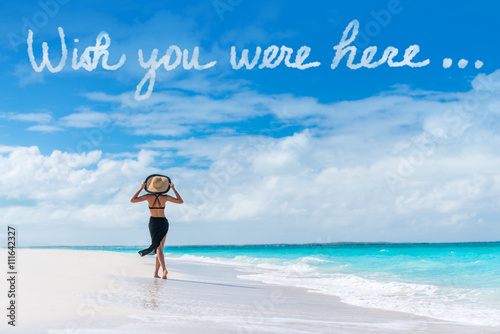 Photo  Wish you were here cloud message written in sky above woman walking on beach vacation Luxury travel Caribbean destination