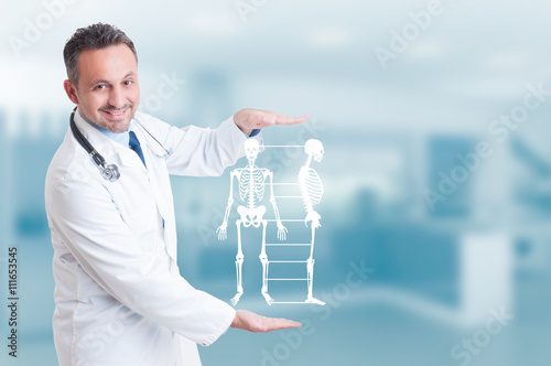 Cuadros en Lienzo Handsome orthopedist doctor holding skeleton model hologram on h