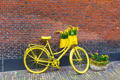 Aluminium Prints Bicycle Vintage vibrant yellow bicycle with basket of daffodil flowers on old rustic brick wall background