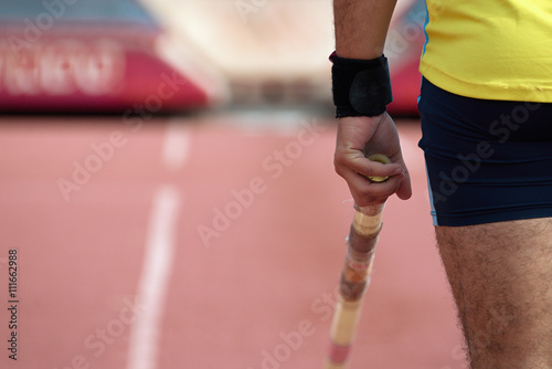 Pole vaulter prepares for jump,looking from behind - fototapety na wymiar