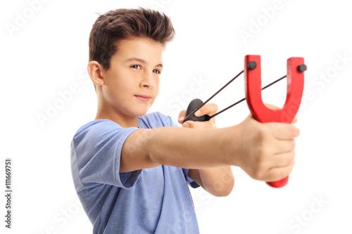 Valokuva  Little boy firing a rock from a slingshot