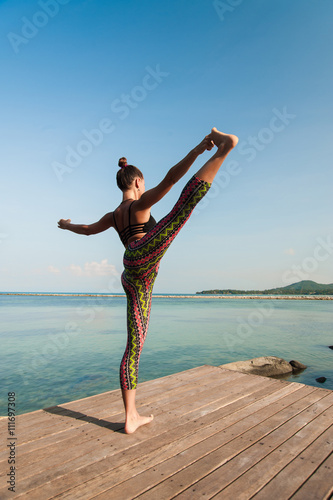 Foto  Woman doing yoga in the morning at the sea.