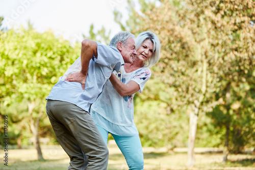 Fotografía  Frau hilft Mann mit Rückenschmerzen im Park