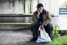 Depressed Homeless Man Sitting On Concrete Wall Under Bridge.
