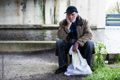 Fotografie, Obraz Depresivní Bezdomovec sedí na betonové zdi pod mostem.