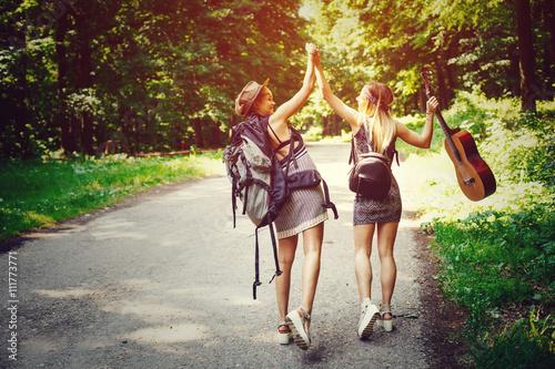 Fotografie, Obraz  Two woman traveler walking along the road through woods