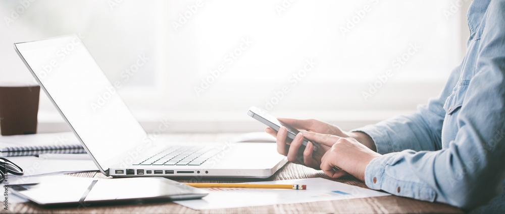 Fototapeta Website developer working using  laptop at the office on wooden
