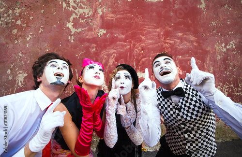 Fotografia  Four mimes point to the top on a red wall.