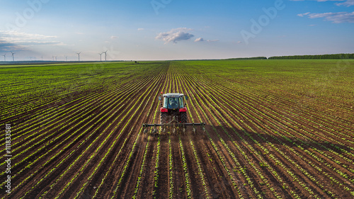 Tractor cultivating field at spring Obraz na płótnie