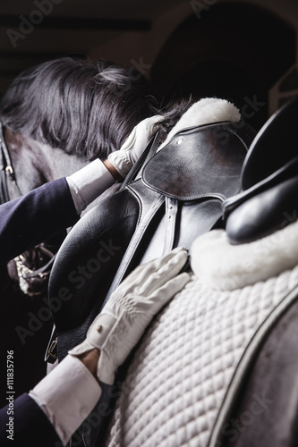 Foto op Canvas Paarden Jockey prepearing horse for the ride