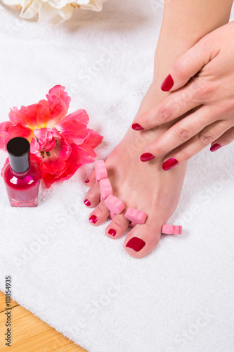 Canvas Prints Pedicure Woman painting her toenails with red varnish