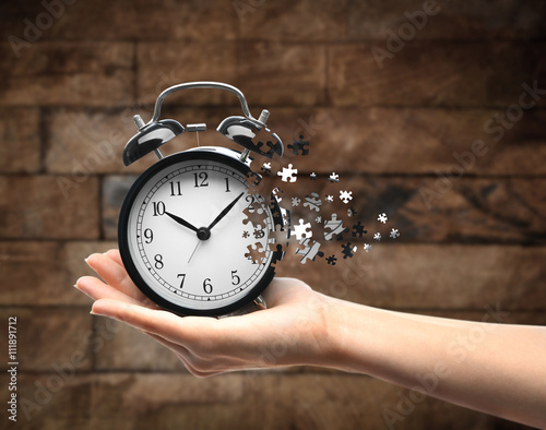 A retro alarm-clock on female hand on wooden background Fototapet