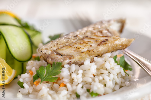 Healthy fish fillet on rice with zucchini