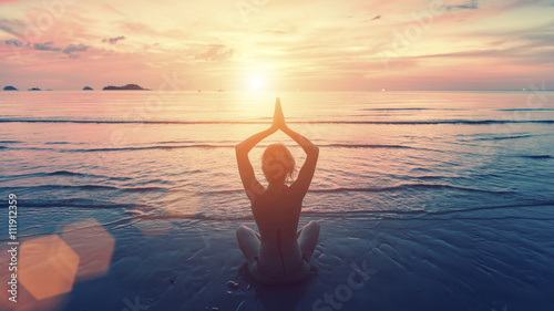 Spoed Foto op Canvas School de yoga Silhouette young woman practicing yoga on the sunset beach. Tranquility and concentration.