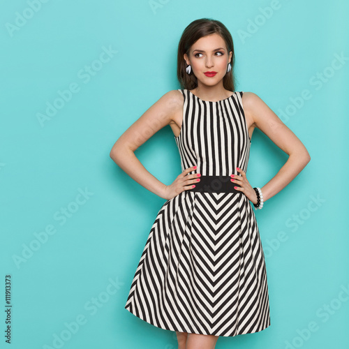 Fotografia  Smiling elegant woman in black and white striped dress posing with hands on hip