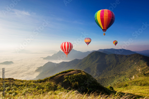 Poster Ballon Colourful hot-air balloons flying over the mountain