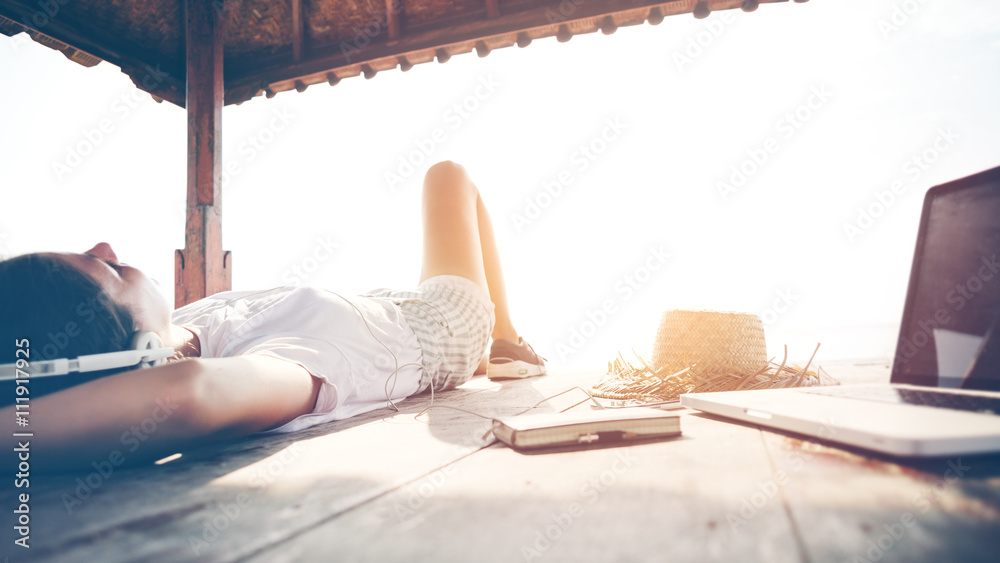 Fototapety, obrazy: Young woman chilling with laptop and listening music with headphones near the ocean. Intentional sun glare and vintage color