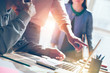 canvas print picture - Business idea discussing. Startup team working with digital project. Laptop and paperwork on the table. Lens flares effect, film effect