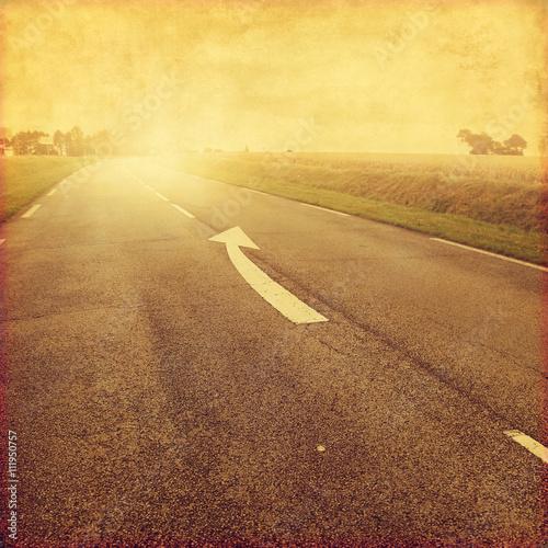 Fototapeta Wiejska droga z strzała znakiem na asfalcie. Grunge obrazu.