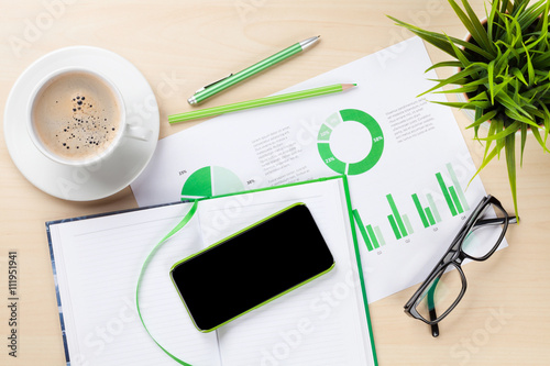 Office desk with charts, coffee, plant and phone - 111951941