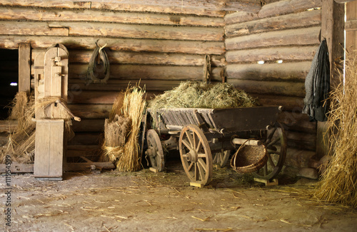Fotobehang Oude gebouw Wooden cart with hay in old barn.