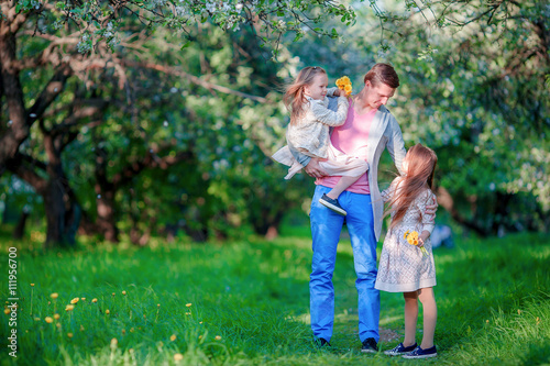 Adorable little girls with young father in blooming cherry garden
