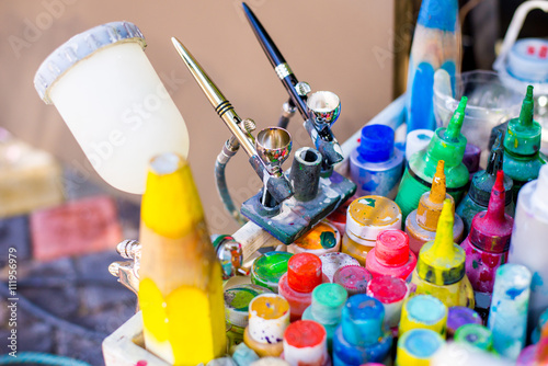 Professional airbrush on a stand with colorful paints in backgroung Wallpaper Mural