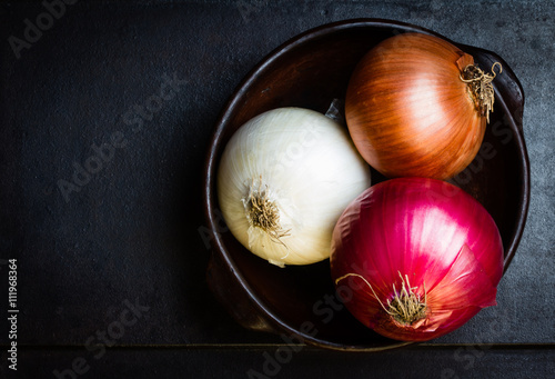 Photo  Different colorful onion in clay bowl on black background